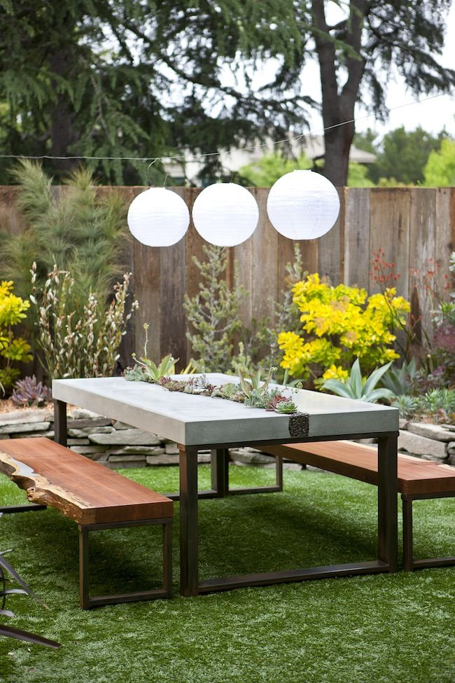 Picnic table in concrete with inset pebble planter -- and thick-cut log-planks as bench seats
