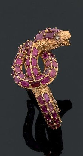 A rare gold, diamond and amethyst snake bangle, French, circa 1840s. The rigid bracelet designed as a coiled snake, with the body set throughout with amethysts, and the eyes set with rose-cut diamonds.