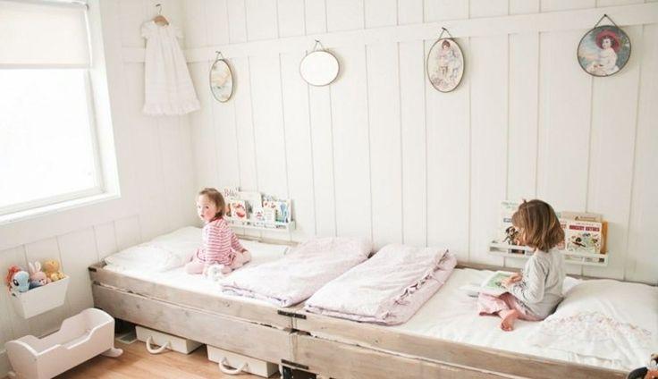 intérieur scandinave dans la chambre enfant avec lambris mural blanc, lits en bois de style rustique et déco murale broderie