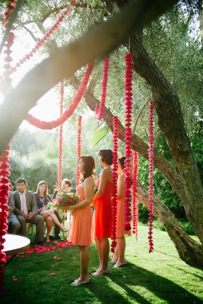 Outdoor wedding - bright flowers strung from the trees  www.weddingsonline,in