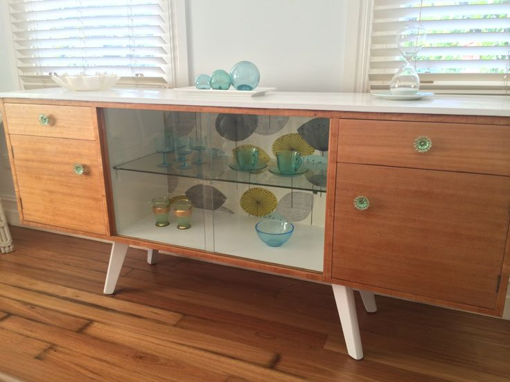 Mid-century buffet with iconic Dandelion Clocks wallpaper lining drawers and cupboards and facing back. LED lights illuminate middle glass display section. Painted white on top. Mid-c with a modern twist! For sale $1350