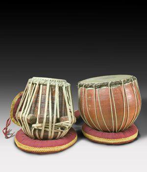 """TABLA  Este nombre, sencillo de pronunciar en casi todas las lenguas, en realidad corresponde a dos instrumentos separados pero unidos en su ejecución y en su historia: el """"bayan"""" o """"dagga"""", que es un tambor fabricado en metal o cerámica, para la mano izquierda, y el """"dayan"""" o """"sidda"""", fabricado en madera excavada, para la derecha. Ambos presentan un parche de piel fuertemente atado con tensores, que a su vez lleva adherido un circulo negro llamado """"shai"""" y fabricado con una pasta hecha a…"""
