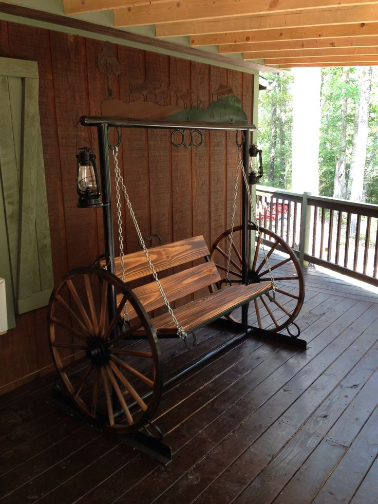 Porch swing with wagon wheel sides and working kerosene lanterns.