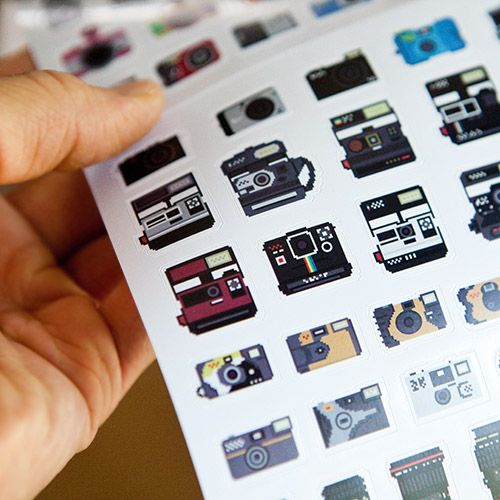 Three (3) sheets of awesome pixelated camera stickers based on iconic cameras ranging from vintage twin-lens reflex cameras to the latest DSLRs!     Beautiful pixel illustrations by designer Billy Brown.