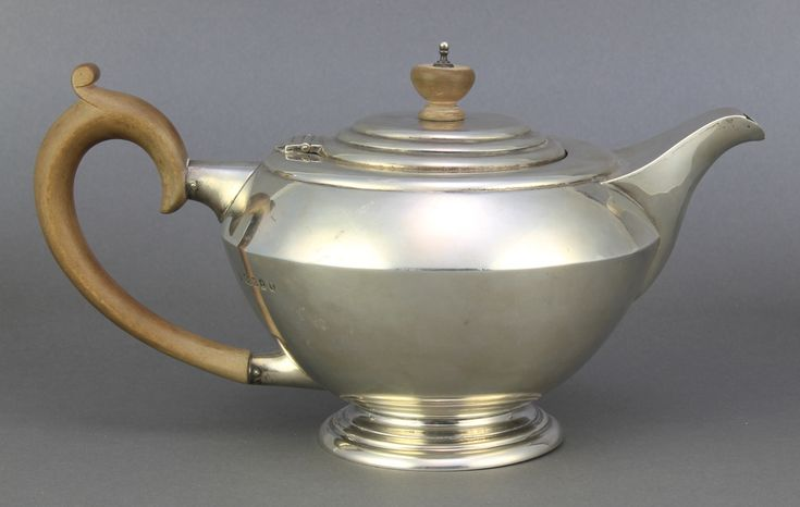 Lot 648, An Art Deco silver teapot with fruit wood mounts, London 1937, gross 564 grams est £120-150