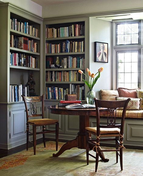 Beautiful bookshelves frame this dining table. I love a multipurpose room!