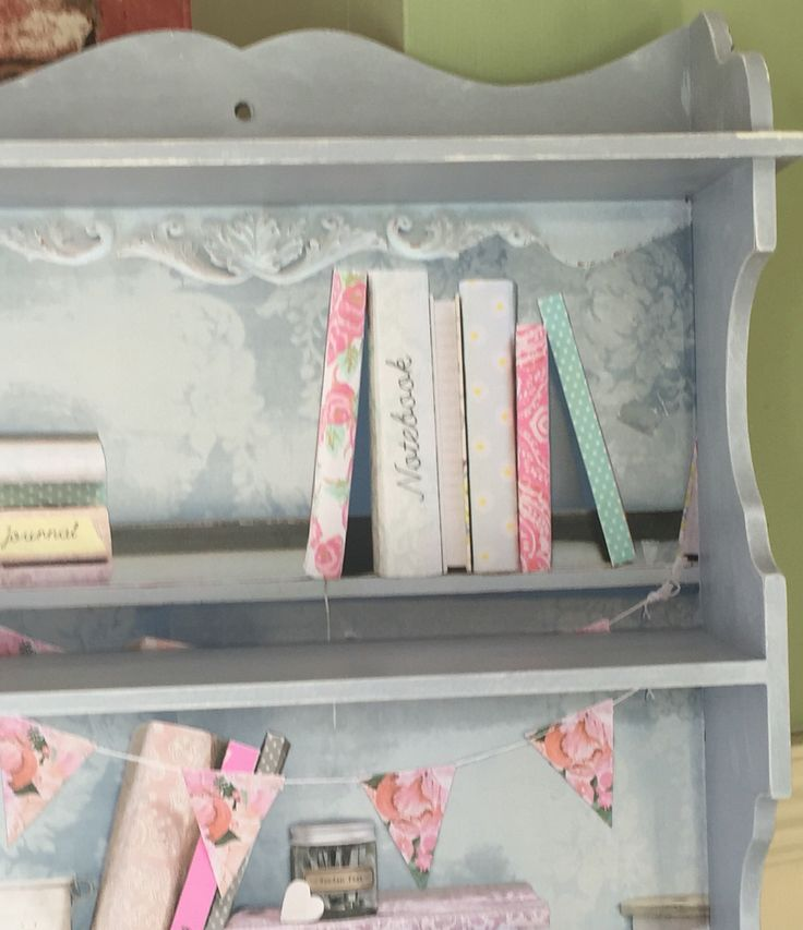 This cute shelf is painted in Autentico French Grey and dry brushed in white , the back is lined with pretty book shelf wallpaper .