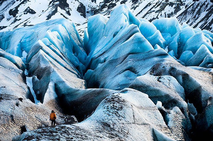 An Extreme Ice Survey (EIS) team member provides scale in a massive landscape of crevasses on the Svínafellsjökull Glacier in Iceland..