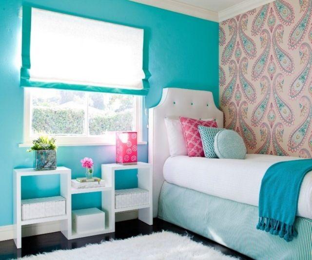 des murs turquoise et un papier peint rose à motifs dans la chambre de fille ado