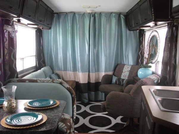 #7 of RV remodel - 1986 Winnebago gets total interior update using dark chocolates & aqua/blues, cabinets were painted dark brown, flooring was replaced with inexpensive laminate flooring, curtains hung behind the driving cabin, painted outdoor rug in a geometric pattern giving space a modern touch; this can be done & so cute.....  DIY Glam RV Remodel with Tufted Wall