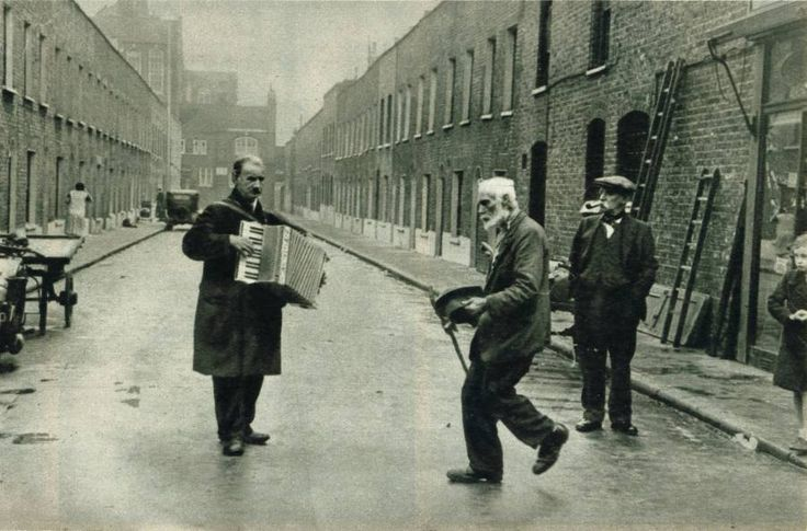 The old man, seen Lambeth Walking at the top of one of the side-streets is a Lambeth institution. He is popular in the Walk, and there are usually a few to give him pennies. Taken from 'Life in the Lambeth Walk' Article.  Source: Picture Post. December 31, 1938