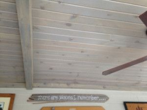Pine tongue and groove porch ceiling in a dusty gray stain with box beams.
