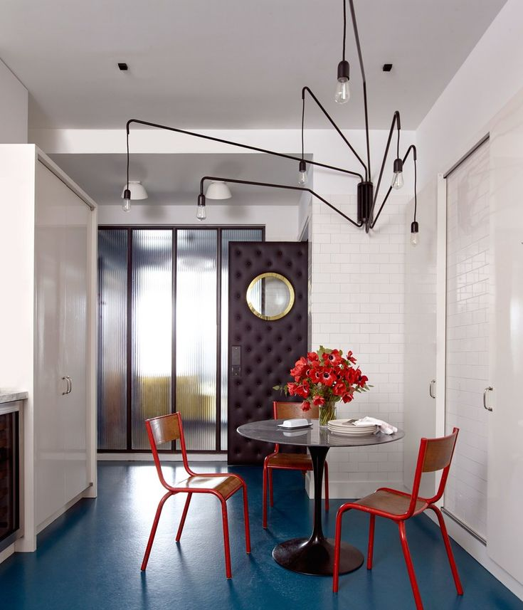 A tufted-leather door, which the owner cites as one of her favorite elements in the house, leads into the kitchen, where Galli again uses her stained blue concrete to create depth. The table, the iconic Pedestal design by Eero Saarinen for Knoll, is surrounded by chairs from the Puces de Saint-Ouen. The light, a show-stopper, is the Lampada 046 wall light with adjustable arms from Dimore Studio.