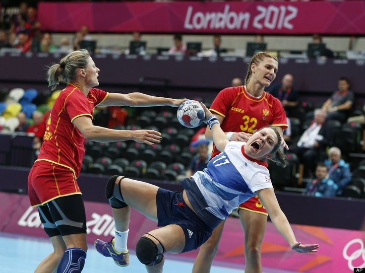 Ewa Palies of Great Britain, center, falls after being tackled by Maja Savic, left, and Katarina Bulatovic, right, of Montenegro during their women's handball preliminary match at the 2012 Summer Olympics, Saturday, July 28, 2012, in London.