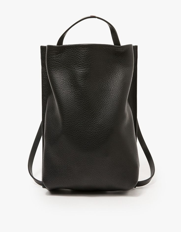 From Chiyome, a large black leather tote pack with minimalist styling.  Features single strap that doubles as top handle or shoulder straps, tab handle, interior back pocket and back panel.  •Large black leather tote pack  •Adjustable strap to functi