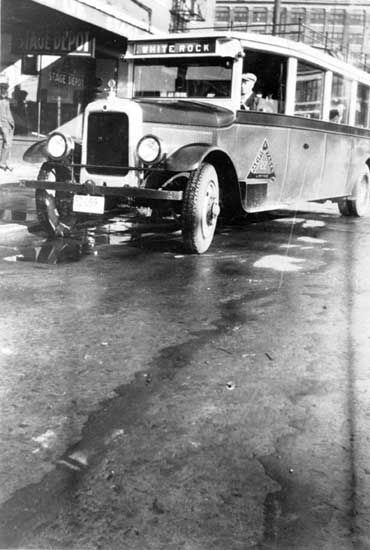 1927 photograph shows the White Rock bus at the Pacific Stage Bus Depot (B.C.E.R. Station) at 8th and Columbia. Driver is probably Norm Phillips. Time to White Rock 1.25 hours. Pacific Stage Depot was at the corner of 8th and Columbia in the old Strand Hotel building. Other occupants of the building were Anderson and Lusby Hardware and Dave Boyle the Barber. The building was torn down about 1932. IHP7854