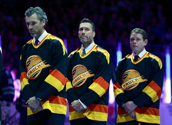Former Vancouver Canucks Trevor Linden Kirk McLean and Pavel Bure listen to the national anthem during their NHL game against the Philadelphia Flyers...