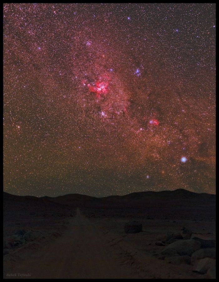 This rugged road through the dark Atacama Desert seems to lead skyward toward the bright stars and glowing nebulae of the southern Milky Way.