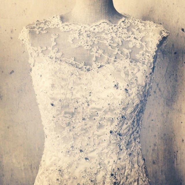 The Dandridge. Fine embellished lace applique over the bodice, the skirts is smooth satin, fishtail cut.  http://www.viva-bride.com/gallery-vintage.html