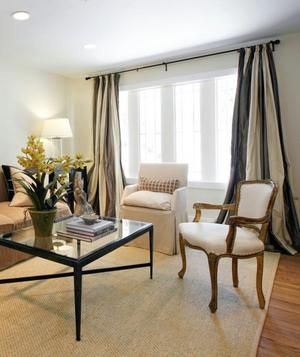 Keep a formal living room from getting too fussy by mixing dramatic accents like these floor to ceiling drapes with everyday classics, like a pair of neutral slipper chairs.