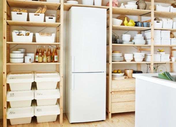 Wooden shelving units built around fridge and containing crockery, foodstuffs and storage bins