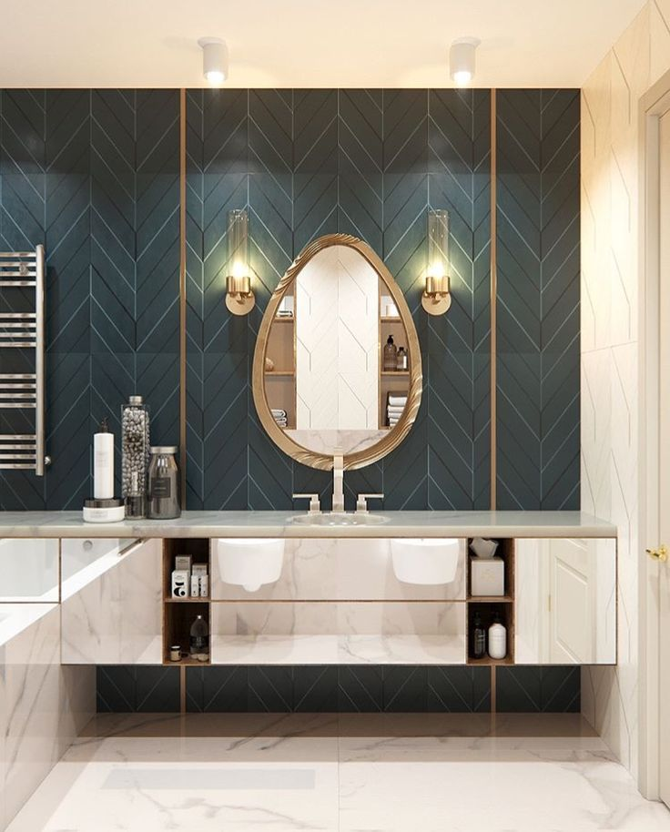Lovely herringbone patterned tile wall in a marble and mirrored bathroom