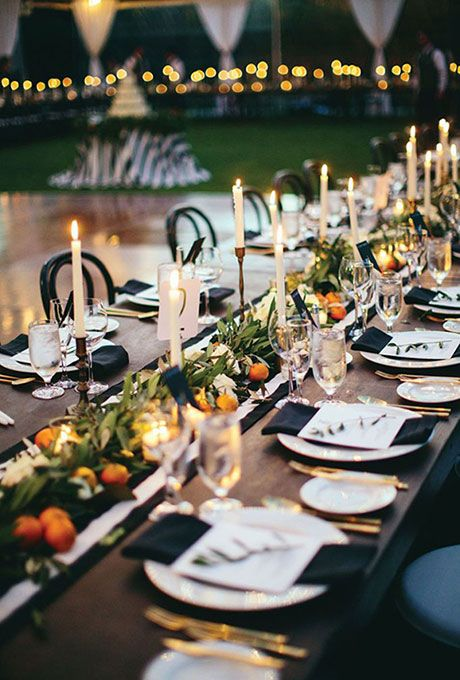 Brides.com: . A greenery and orange garland stands out against this elegant black-and-white reception table.