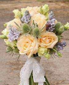 Delicate, lacey, hand-tied bridal bouquet - perfect for a vintage tea-party. Peach roses, scilla (bluebells), lisianthus and eryngium thistle. Florissimo, Shropshire