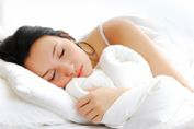 A woman asleep on a bed on her right side (facing the camera), with a white duvet and pillow. Ref: www.dreamstime.com