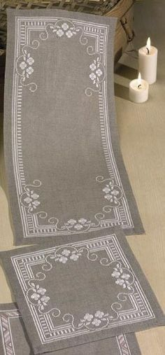 Crisp white flowers with swirls and a geometrical border make these lovely mats special.