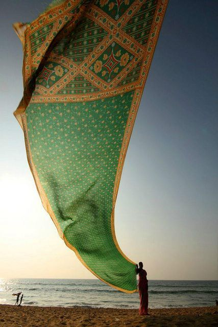 woman drying her saree on  Konark beach. Konark Beach is situated in Odisha on the eastern coast of India and is considered to be India's finest beach.