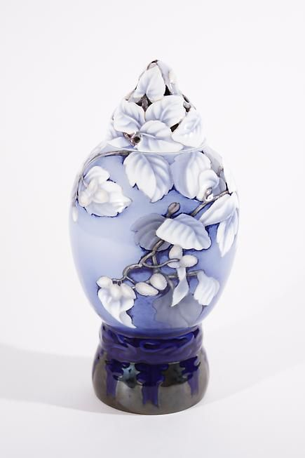 Bing & Grøndahl covered porcelain jar on raised stand. The jar in pale to dark blue ground decorated with white leaves and pinecone branches, the reticulated cover with leaves and pinecones, signed with firm's mark and initials for designer Effie Hegermann Lindencrone. c1902