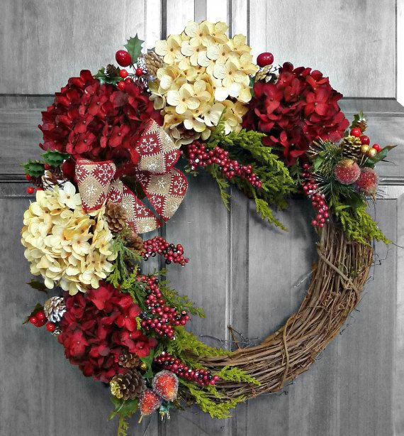 A Christmas wreath on your front door adds so much to the seasons excitement when planning your Christmas home decor. As a child, it added to the joy of the season to enter a home already decorated at the door. That same feeling remains today and I love creating that feeling of magic at Christmas! Five burgundy and cream hydrangea blossoms create a stunning and festive wreath! Frosted pears, berries, snow dusted pine cones, evergreen foliage, and a red and tan burlap snowflake bow have been…