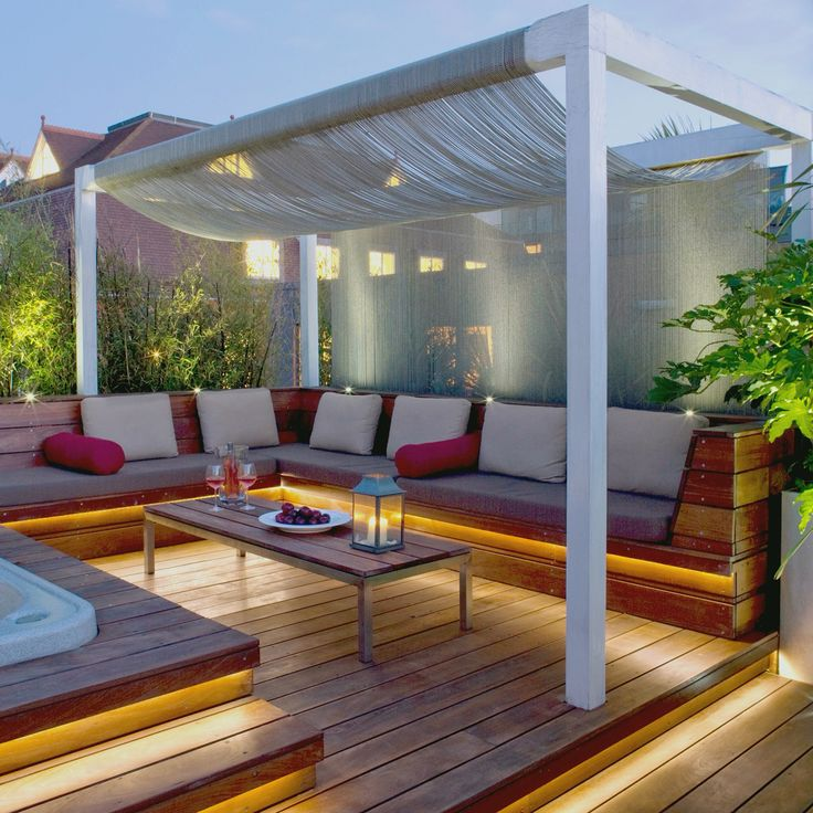 Roof terrace landscape decking hot tub jacuzzi external concealed lighting planting bamboo exotic frame cushions red patio deck spa wellbeing zen curtains drapes oak posts Clerkenwell London  penthouse lifestyle chill party pad