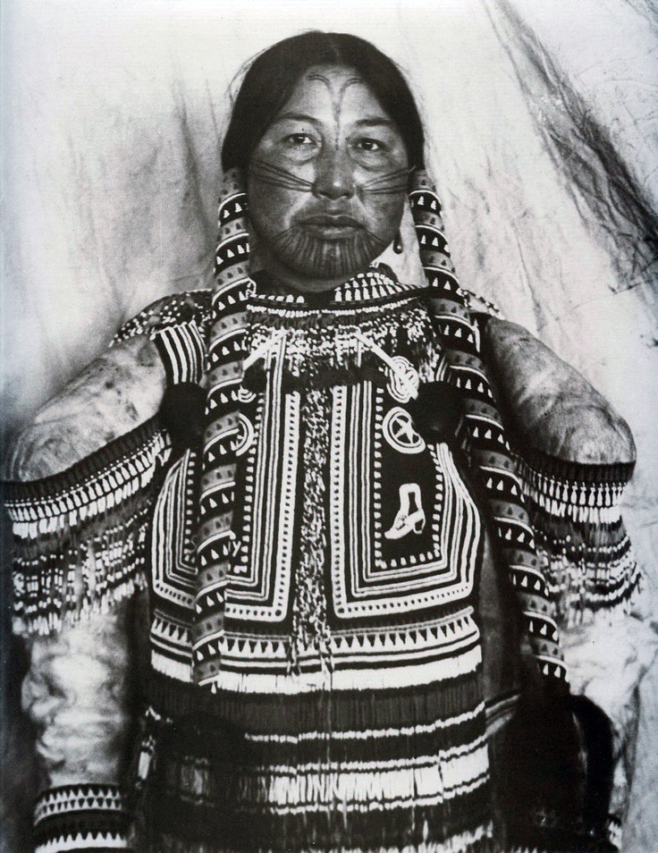 Canada ~ Northern Territories | West Arctic Inuit Woman. Her clothes and braids are heavily decorated with beads and other trade items.  Mackenzie River Valley, western coast of Hudson Bay | Photograph by Albert Peter Low.  ca. 1903/4
