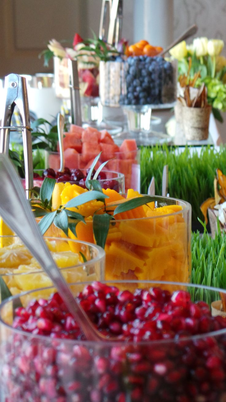 An extraordinary smoothie bar featuring glass vessels brimming with succulent fresh fruits, surrounded by wheat grass and fresh herbs.
