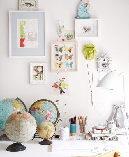 a nice mix with all white frames and a few objet d'art-- I like the addition of one pale blue mat.