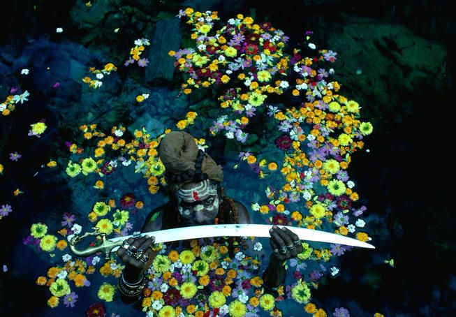 Nepal -  Sadhu, or Hindu holy man, displays a sword in a pool of water surrounded by flowers.