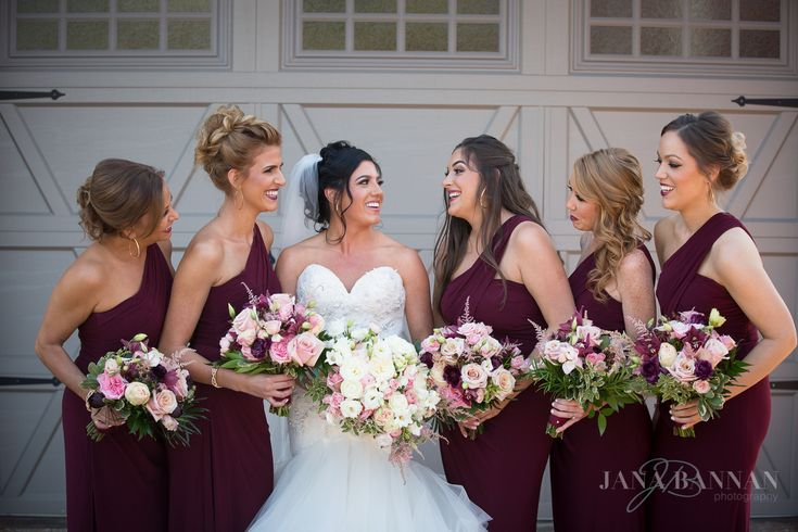 The bridesmaids celebrating Erika and Mike's wedding day carrying bouquets of blush, pink, merlot, and cream to accent their burgundy dresses. Jana Bannan Photography.