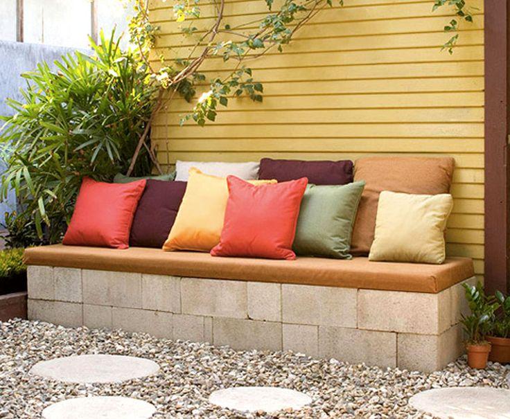 Enkelt bygge av sittbänk med staplade betongblock och mjuka kuddar.
