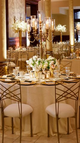 Gold metal candelabras with elegant taper candles in glass hurricanes surrounded at the base by clear cylinder vases- 1 with a re-purposed bridesmaids' bouquet and the other 2 with similar arrangements of cream hydrangeas, ivory polo roses, white sweet peas and white/green parrot tulips.