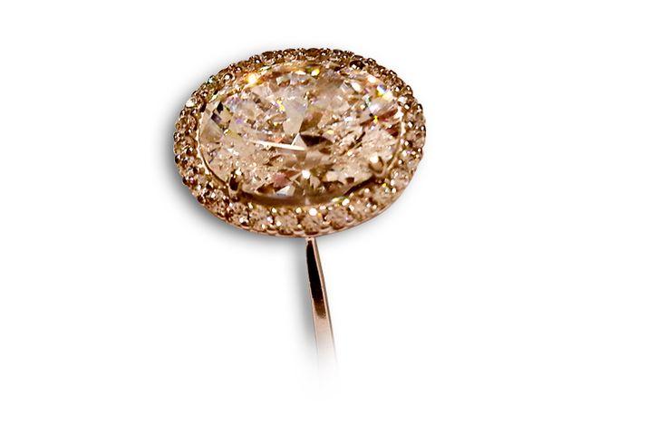 18 KARAT WHITE GOLD AND OVAL DIAMOND ENGAGEMENT RING.