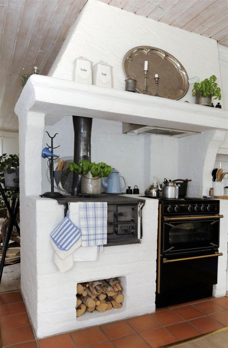Köket har plats för både vedspis och elspis. Blå emaljföremål och kökstextilier i blått är pigga accenter mot den vita basen.