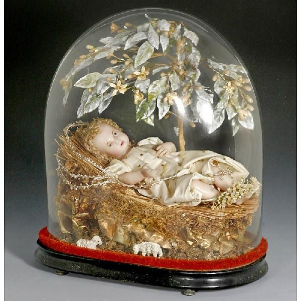 Wax Crèche Figure Under Glass Dome  With finely-modelled shoulder head, arms and legs, cloth body, blue glass eyes and open/closed mouth with two tiny inset teeth, draped in robe of cream-colored satin, lying on straw in a crib of gold-painted paper and dried moss, under paper-stemmed tree of wax flowers and fabric leaves with dusting of 'snow', figure approx. 12 in., 30 cm, under an earlier glass dome on ebonized base, height: 17 in., 43 cm