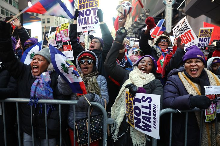 "Protesters carried Haitian flags and signs like ""peace, love, power, dream&..."