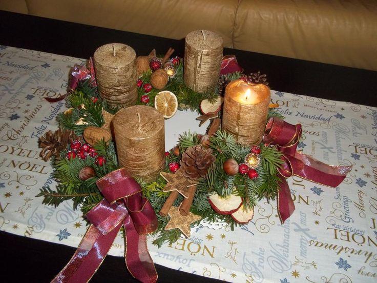 Adventskranz aus gemischtem Grün auf einem Strohrömer gewickelt mit goldfarbenen Kerzen und roten Schleifen. Die Kerzen wurden jeweils mit vier 5 cm-Stücken blaugeglühtem Stahldraht in der Unterlage festgesteckt. Die Naturmaterialien sind mit der Heißklebepistole festgeklebt.