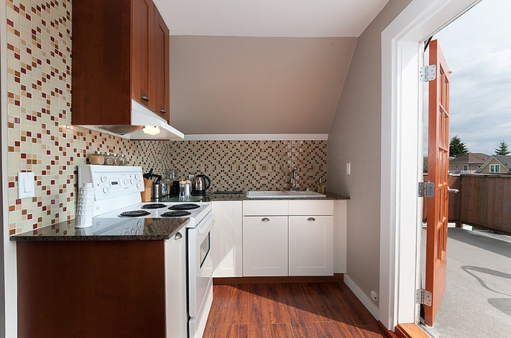 The kitchen fits perfectly in a sensible layout where the cooking area is easily maneuverable and nicely accented with a glass-tile mosaic back-splash.  #CommercialDrive #Rentals #Luxury