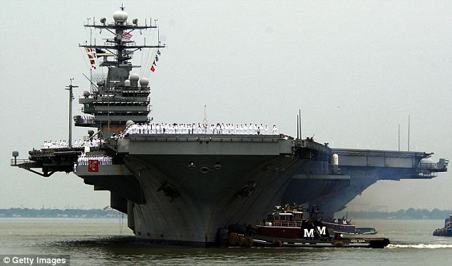 The giant aircraft carrier is assisted by tugboats into its home port at Norfolk Naval Station, Virginia, in May 2003, before heading to the...