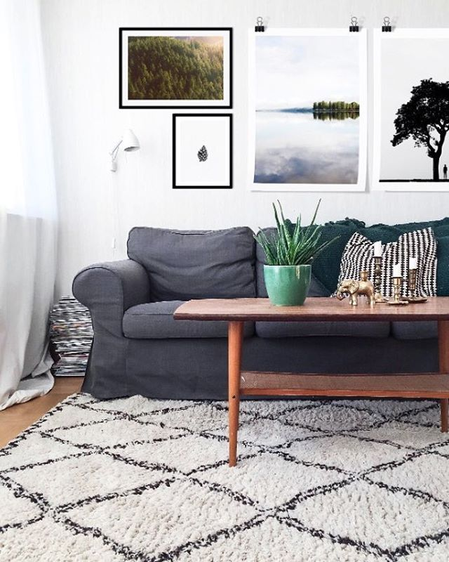 Modern living room with black and white rug, wooden floors, teak table and both posters and framed posters from @printler , the marketplace for photo art.