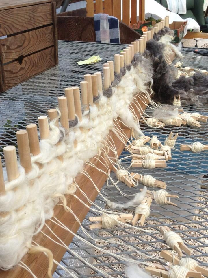 Peg loom -- weaver is using fleece for the weft.  Look how the warp is handled!  looks like clothes pegs!